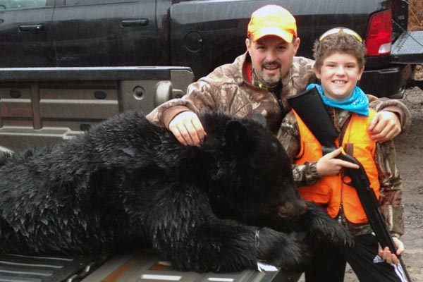 Clare Justin and Jackson Hooper with a 200-pound black bear taken in St. Lawrence County